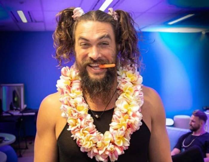 Момоа появился на австралийском телешоу The Project TV с двумя заплетенными на голове косичками в стиле школьницы и с гавайским венком на шее.